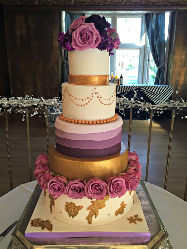 Purple and gold wedding cake with fresh flowers